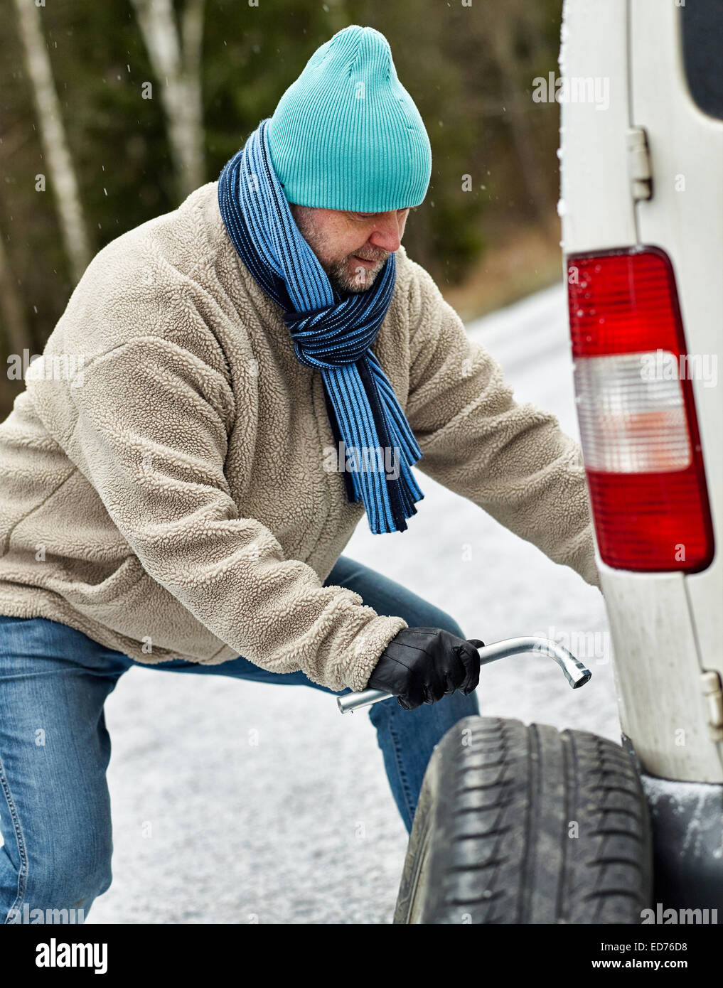 Mid adult man exchanging tire on the road - Stock Image