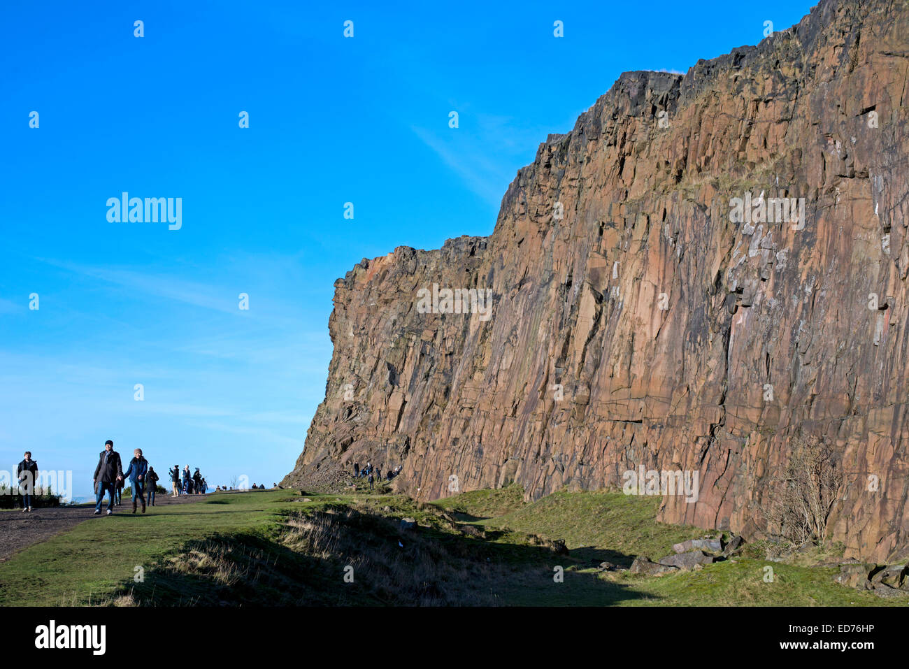 Locals and tourists enjoying a winter stroll along the Radical Road beneath Salisbury Crags in Edinburgh's Holyrood - Stock Image