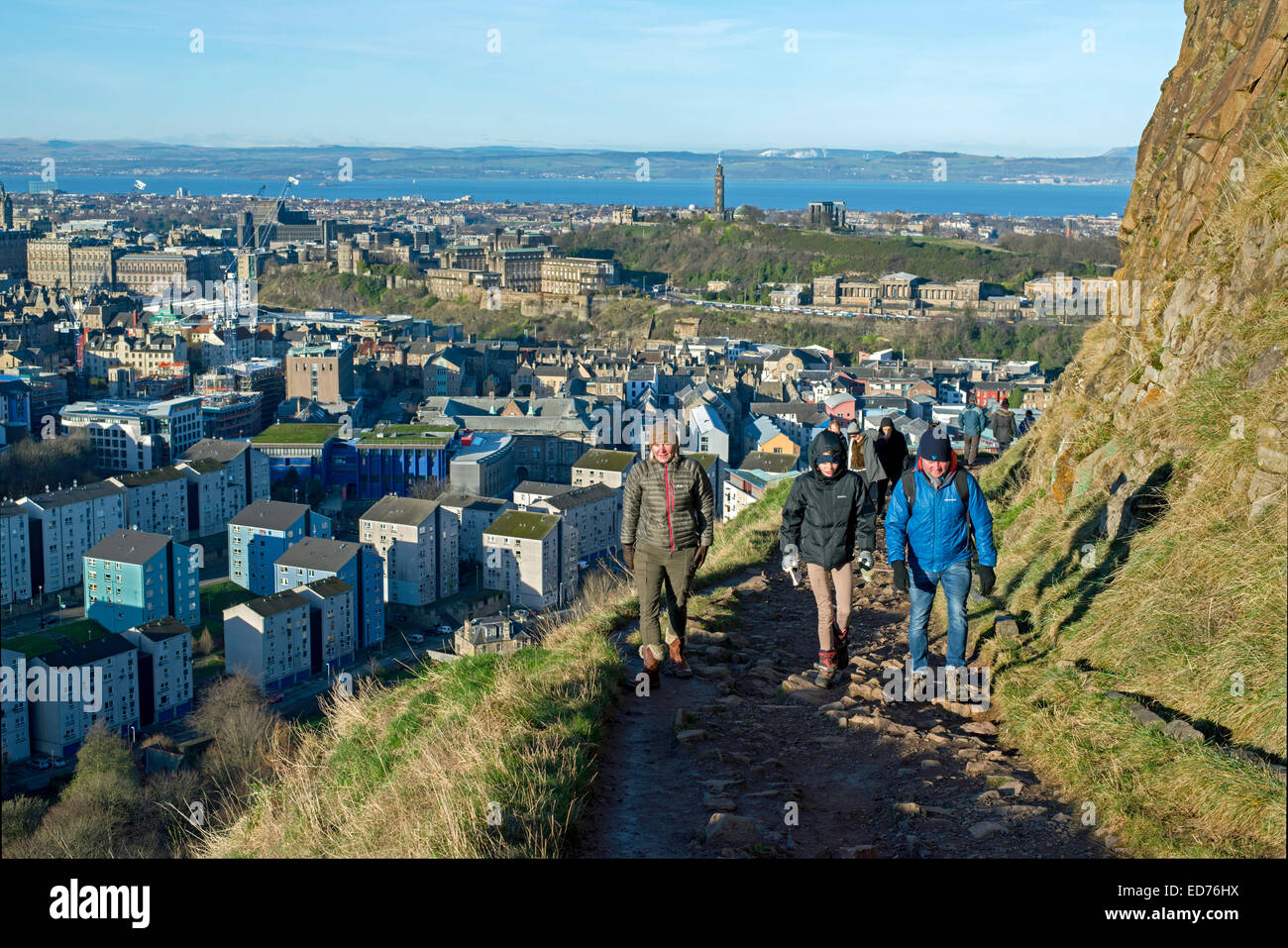 Walkers on the Radical Road beneath Salisbury Crags with the city of Edinburgh in the background on a sunny winter's - Stock Image
