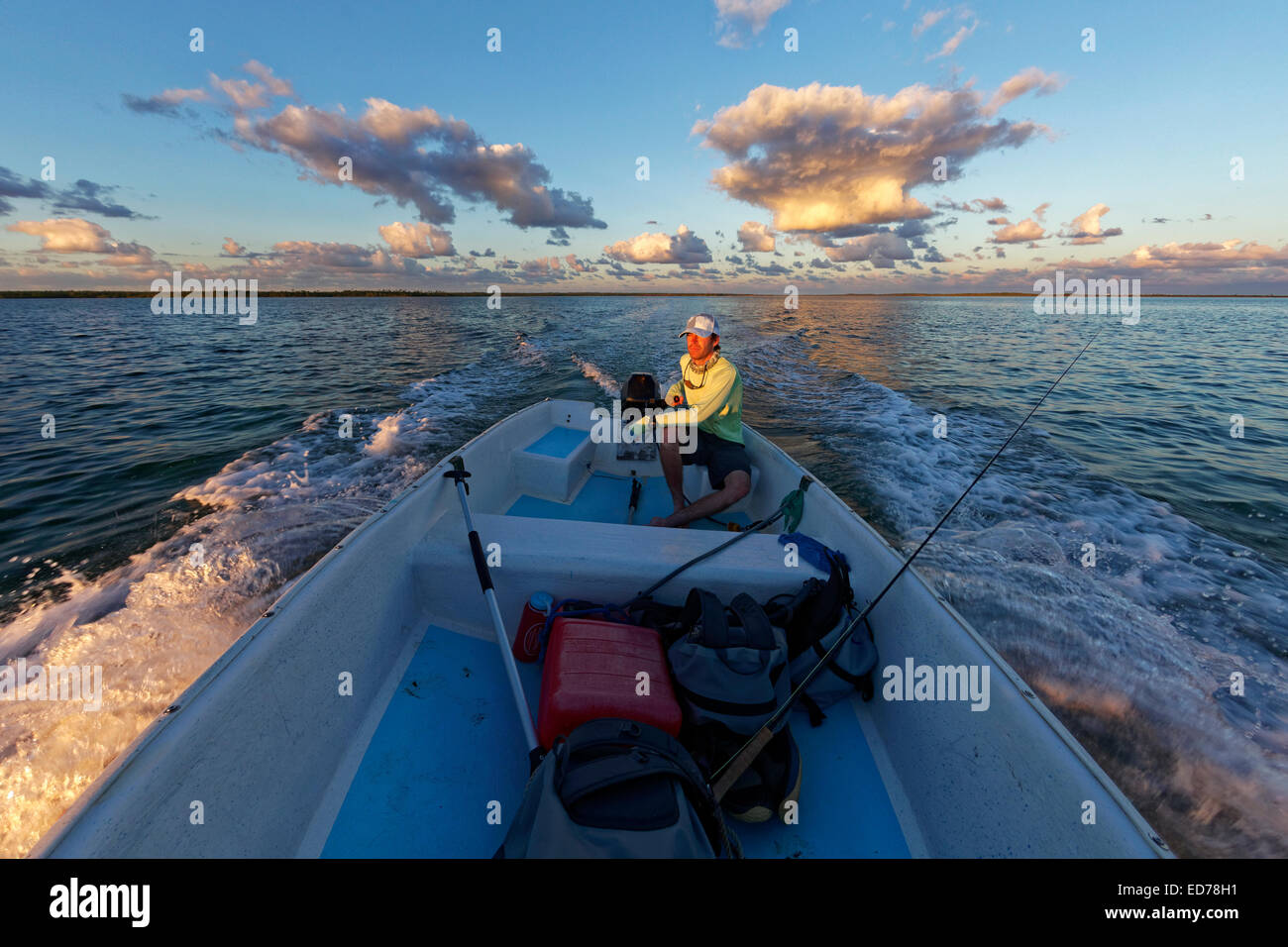 Fisherman driving small boat at sunset, abaco, bahamas - Stock Image