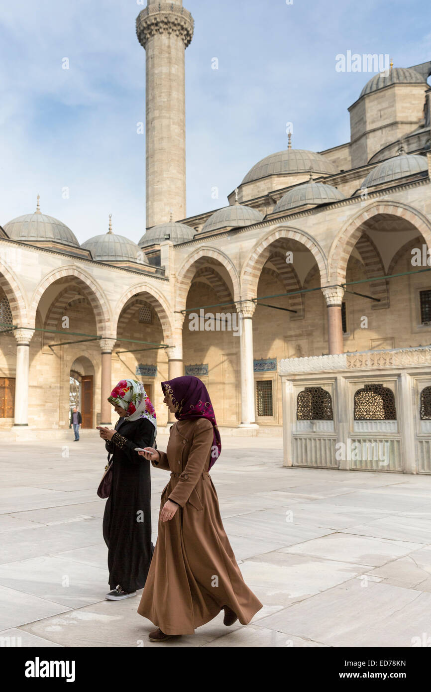 Muslim women in veil and modesty clothing in courtyard of Suleymaniye Mosque, Istanbul, Republic of Turkey - Stock Image