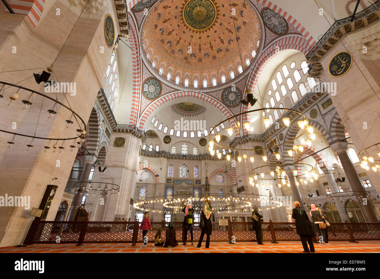 Tourists wearing scarves in interior of Suleymaniye Mosque in Istanbul, Republic of Turkey - Stock Image