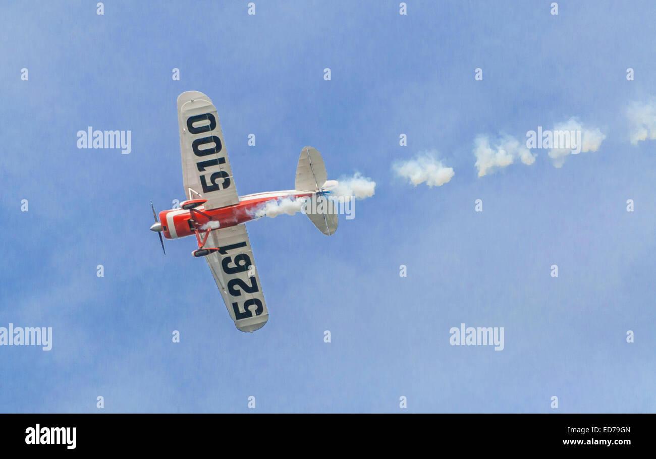 bi plane in sky with emission skywriter - Stock Image