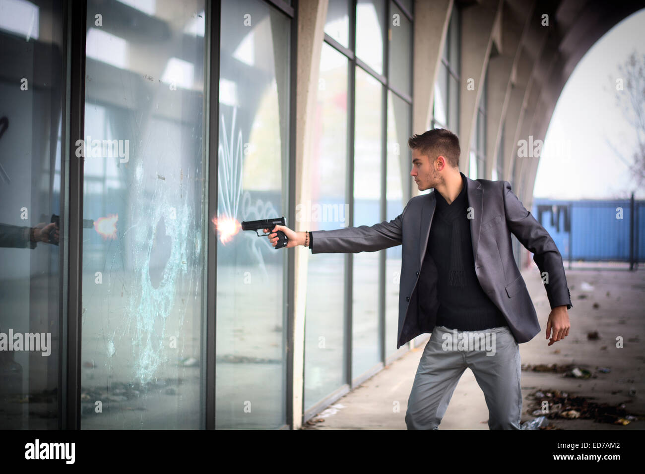 Young detective or policeman or mobster firing a gun to a window glass - Stock Image