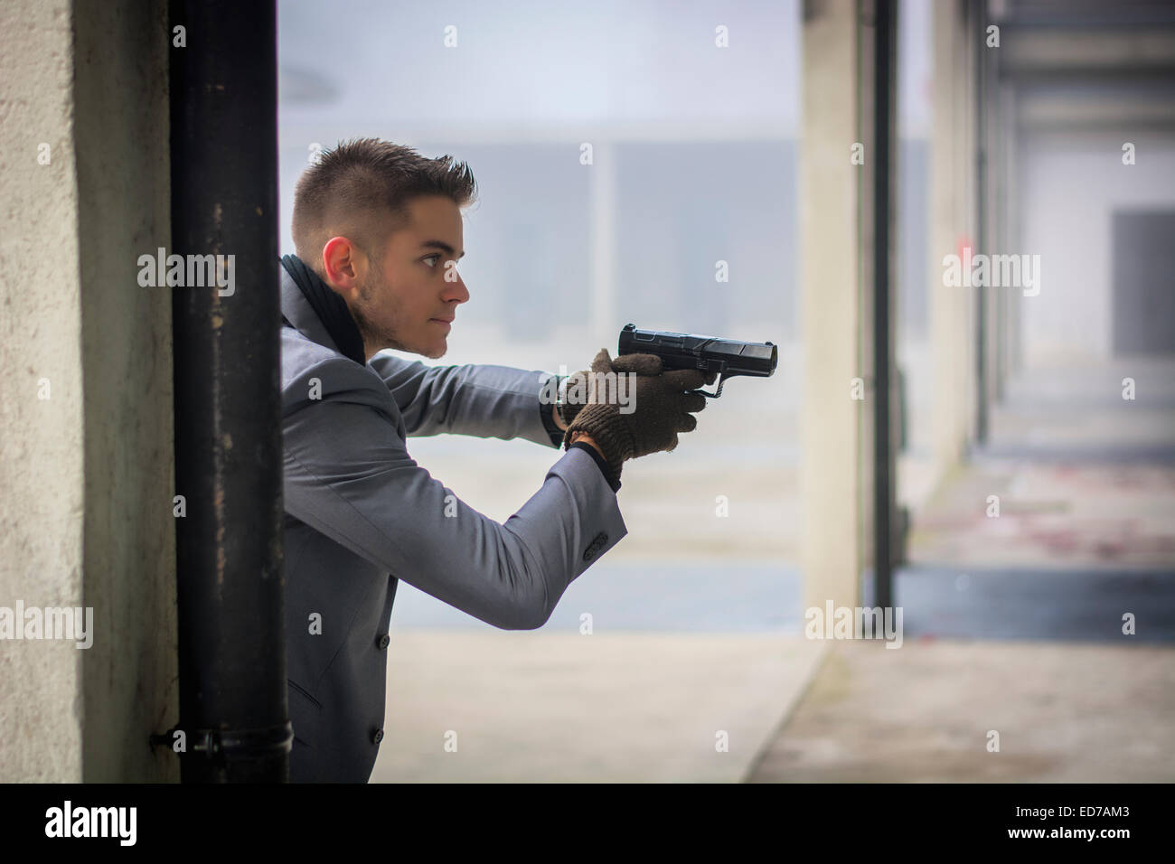 Well dressed handsome young detective or policeman or mobster holding a gun - Stock Image