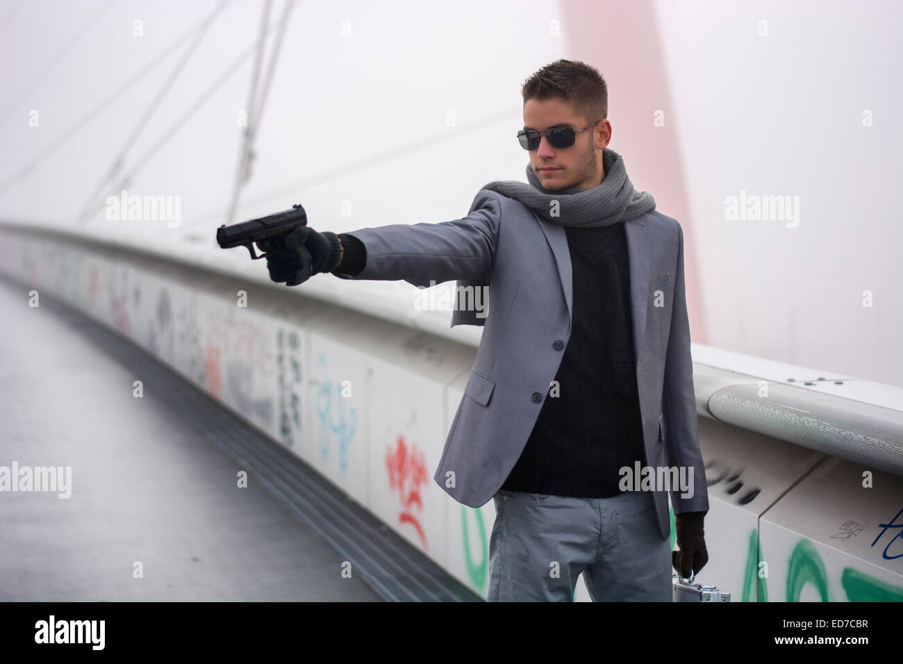 Young detective or policeman or mobster firing a gun - Stock Image