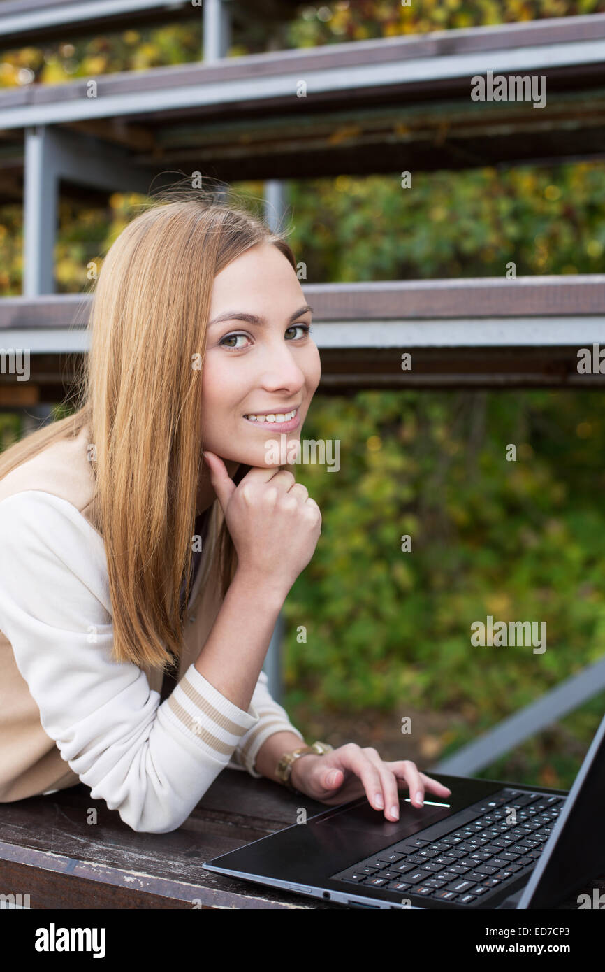 Student lying on sport tribune and doing something on laptop - Stock Image