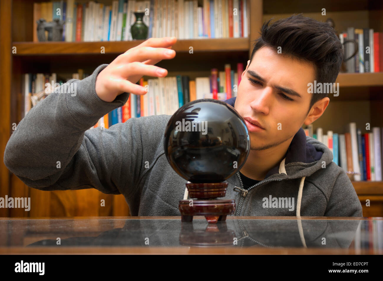 Young man predicting the future by looking into crystal ball - Stock Image