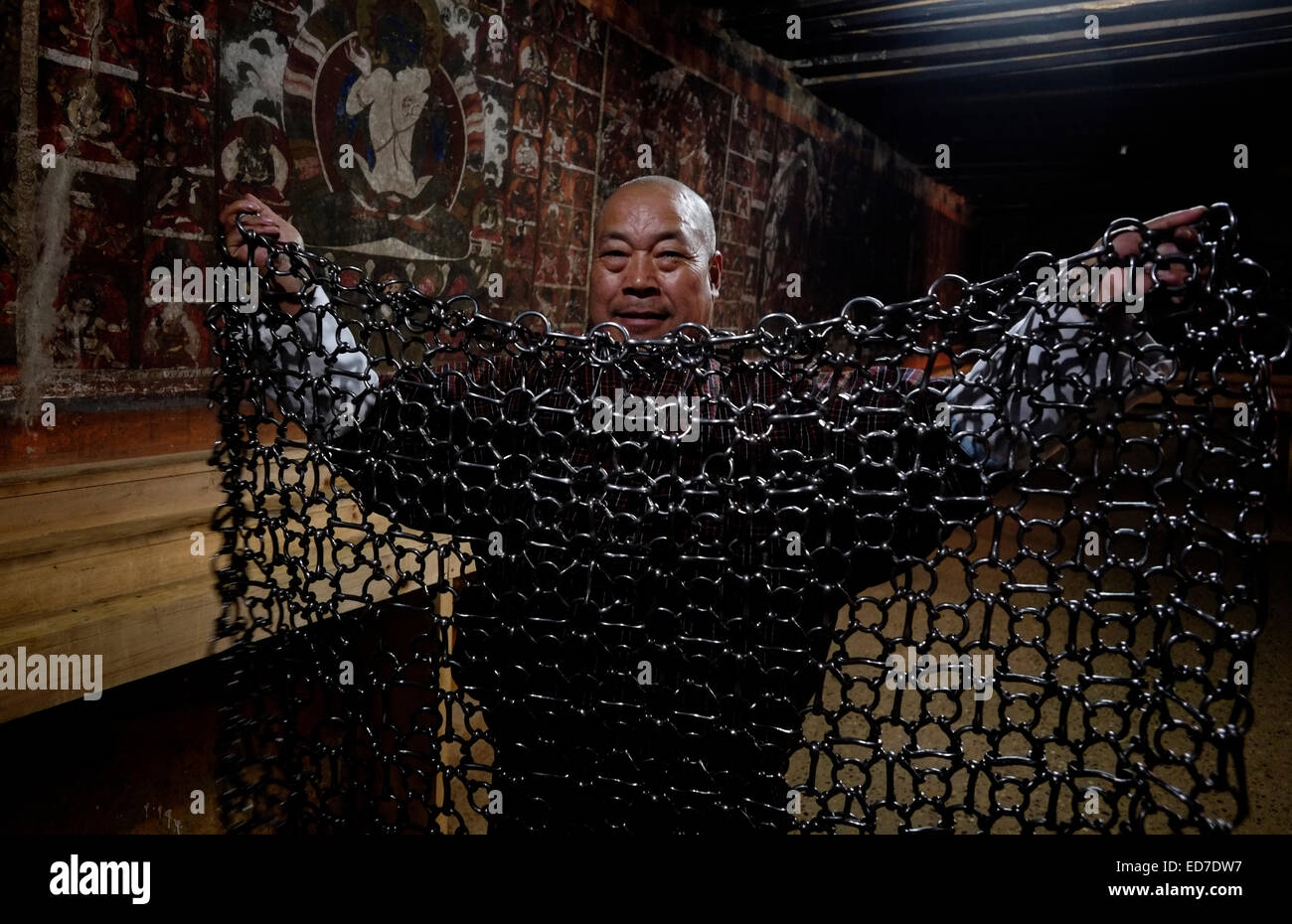 A Buddhist devotee spreading a heavy chain-mail coat which was made more than 600 years ago by the revered Buddhist - Stock Image