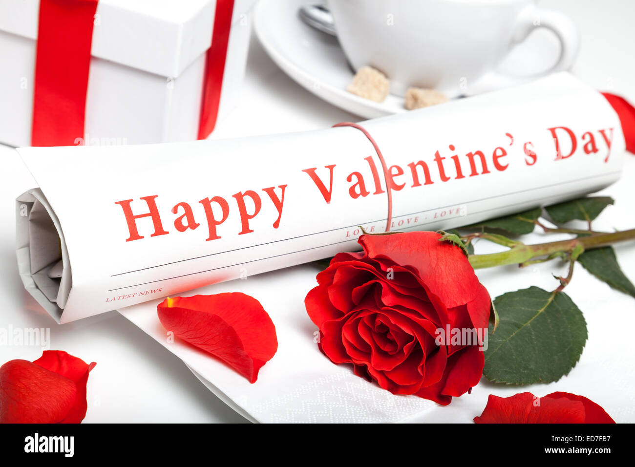 'happy valentine's day' newspaper, red rose and present box - Stock Image