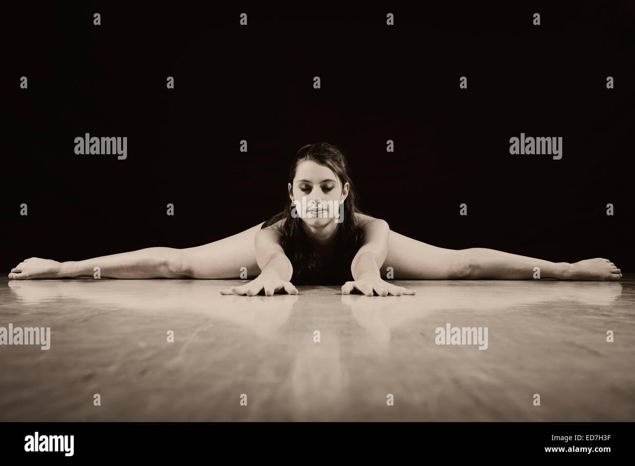 Young woman doing the splits, acrobatics - Stock Image