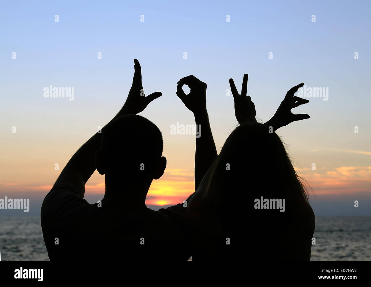 A Silhouette Of A Romantic Couple Holding Their Hands Spelling The Word Love On