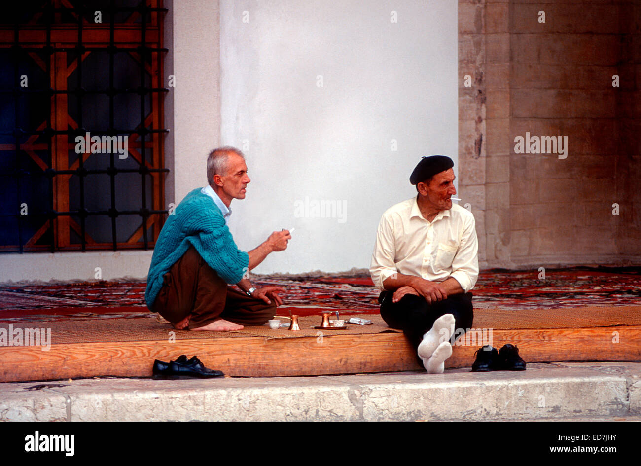 Sarajevo, Bosnia. Men drinking coffee and smoking on steps of Gazi Husref Beg Mosque. - Stock Image