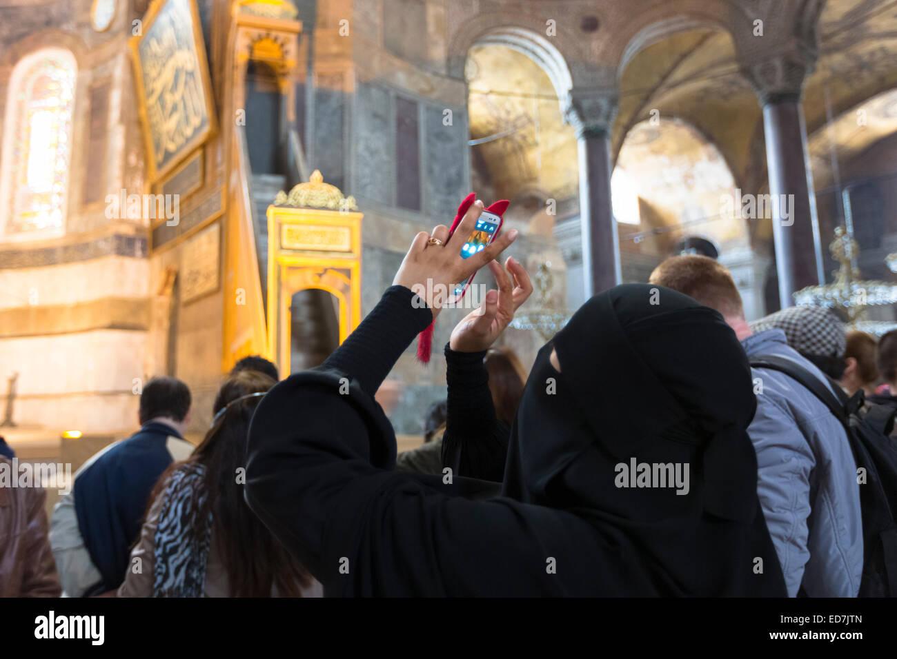 Muslim woman at Hagia Sophia, Ayasofya Muzesi mosque museum wearing niqab using smartphone to take photographs, - Stock Image