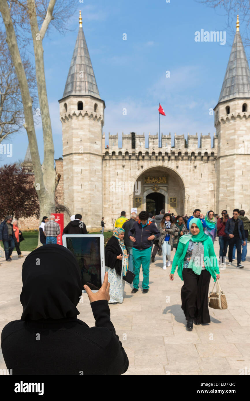 Muslim woman taking photograph with iPad tablet and tourists at Topkapi Palace, Topkapi Sarayi, in Istanbul, Republic - Stock Image