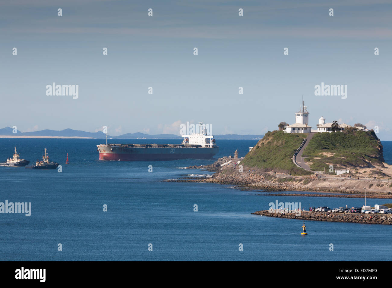Bulk Carrier Ikan Kedewas passing the Nobbys Head Lighthouse as it approaches its berth in Newcastle NSW Australia - Stock Image