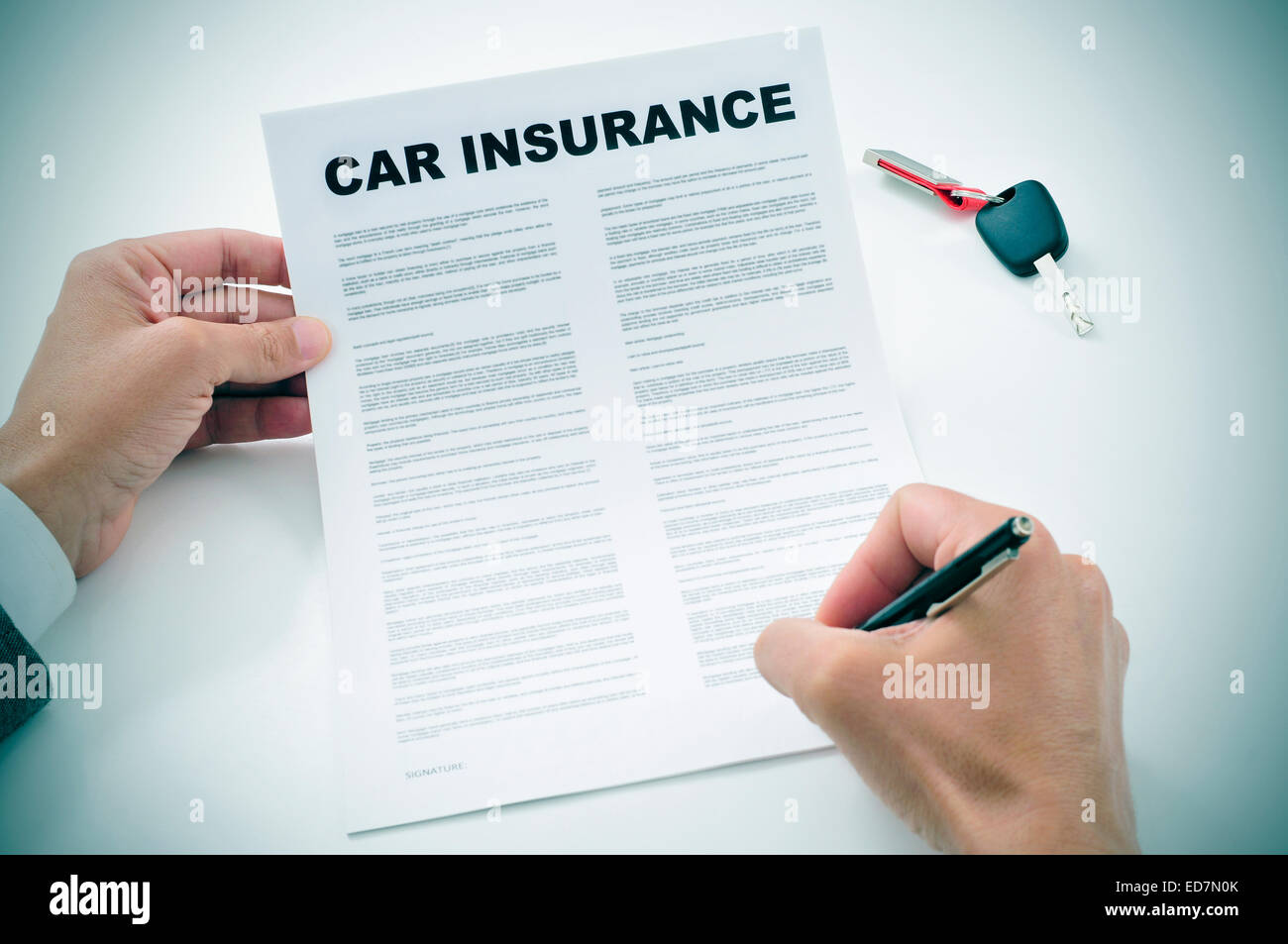 closeup of a young man signing a car insurance policy - Stock Image
