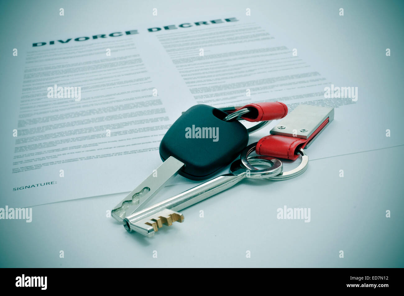 a divorce decree document and the keys of a car and a house - Stock Image