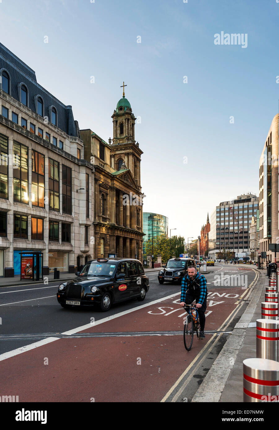 On Holborn Viaduct looking toward Holborn, a cyclist rides down a bus lane, London Black Cabs pass by - Stock Image