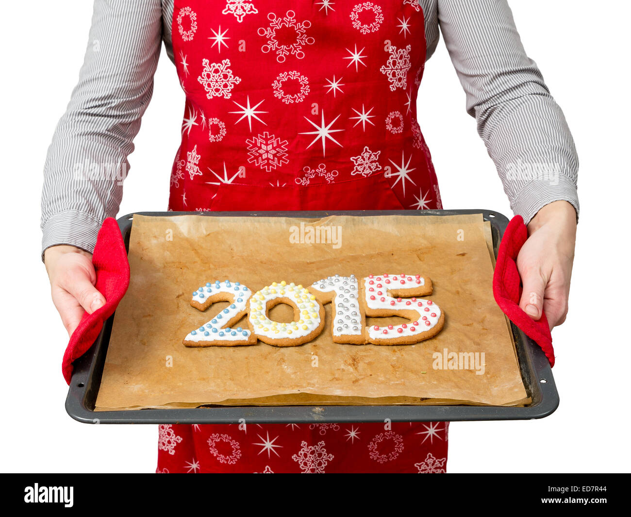 Woman wearing red apron holding home-made gingerbread cookies in shape of 2015 New Year digits on baking tray shot - Stock Image
