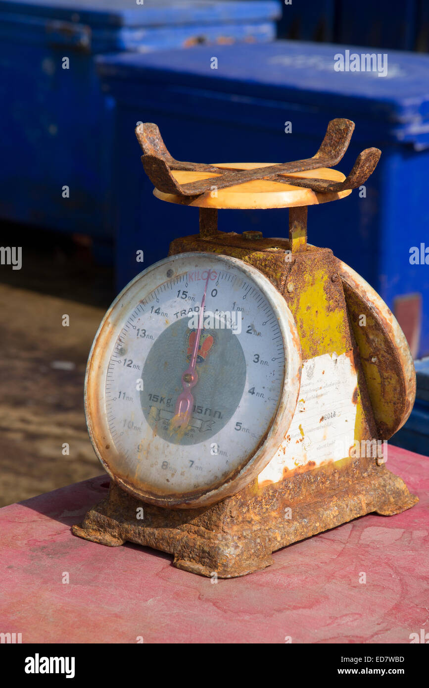 Rusting metal scales in use in a fish market Thailand - Stock Image
