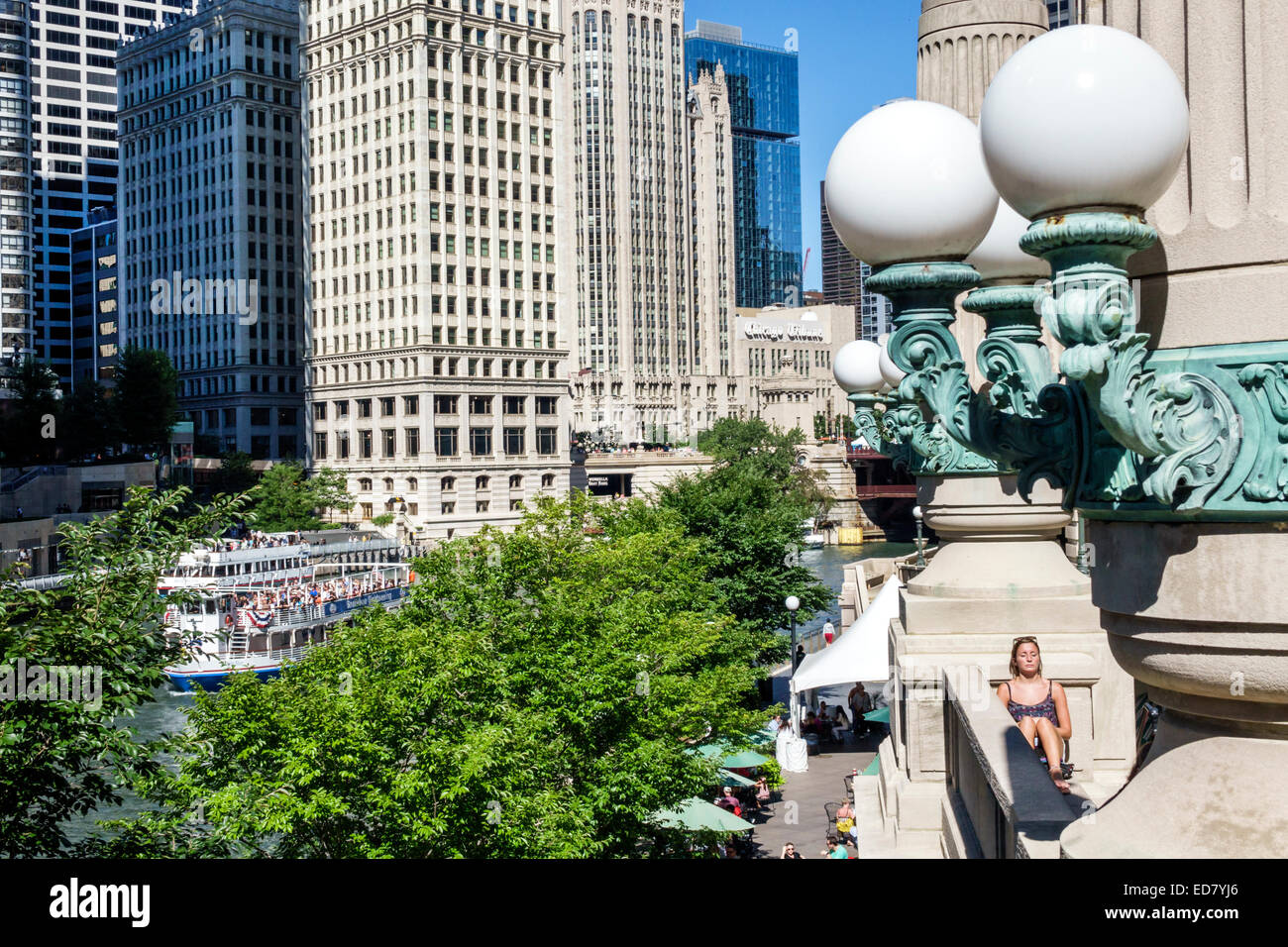 Chicago Illinois Chicago River downtown Wrigley Building city skyline skyscrapers Riverwalk resident woman sunning - Stock Image