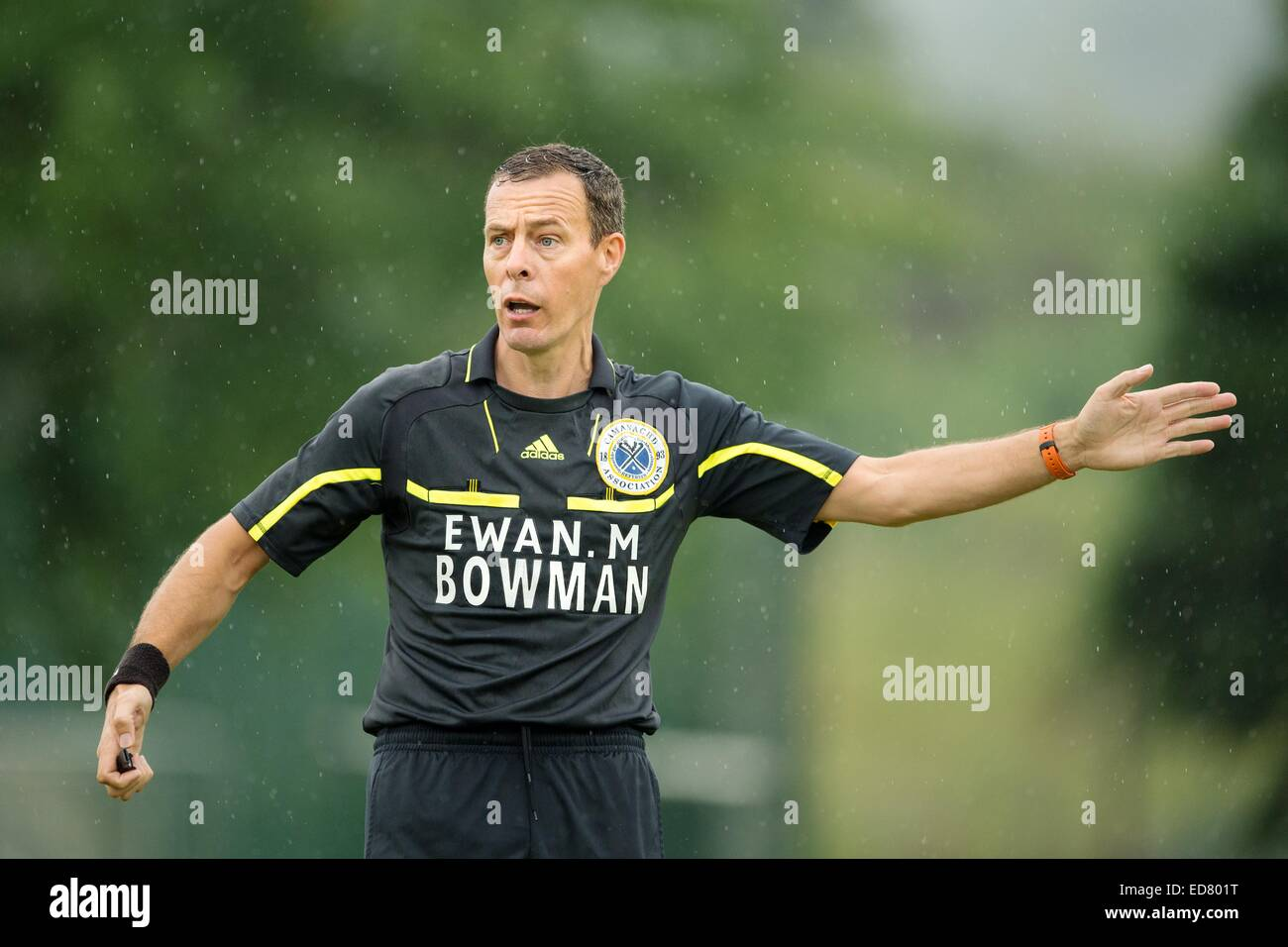 Camanachd Association shinty referee Deek Cameron from Fort William in action in the rain. - Stock Image