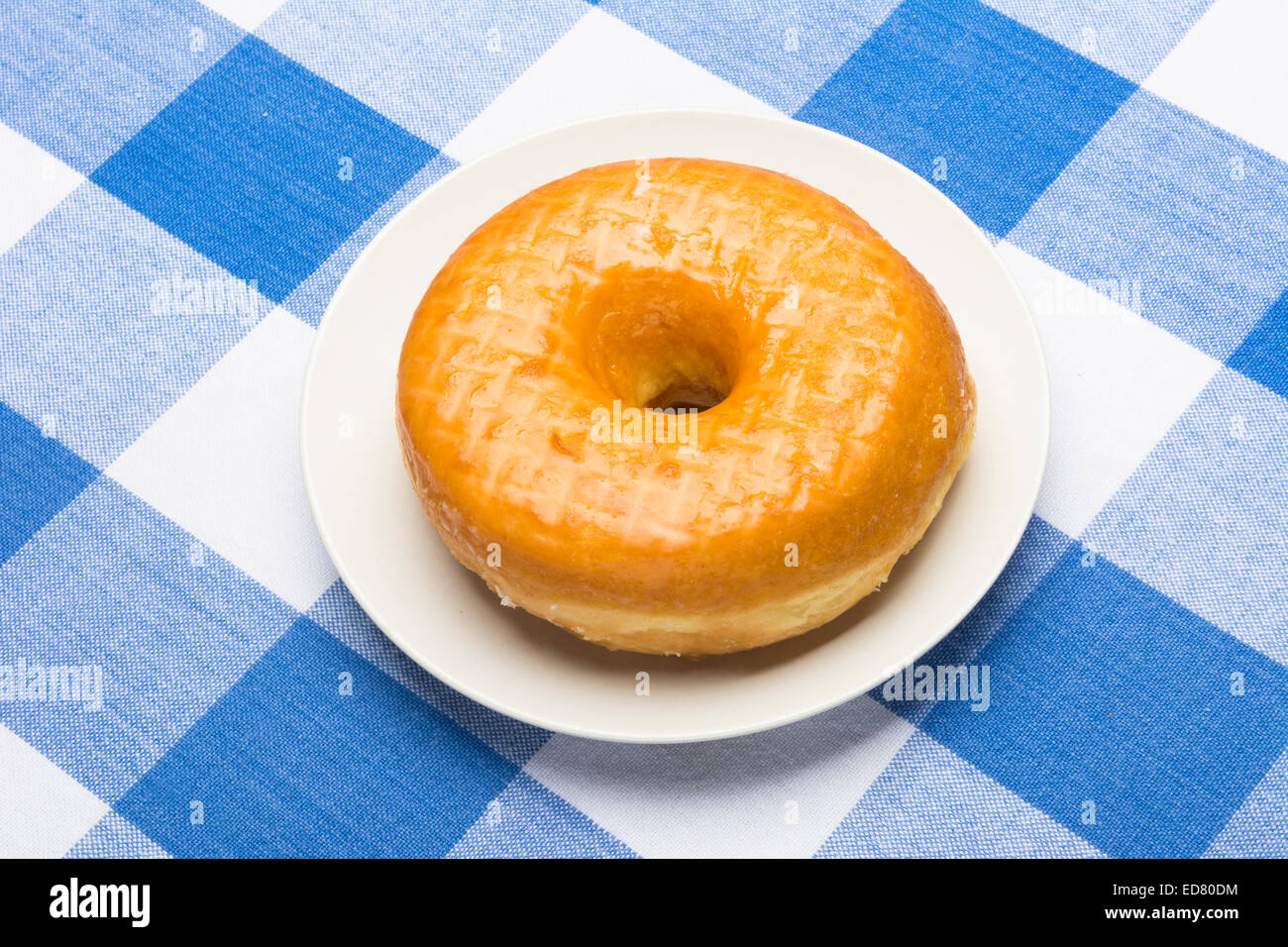 A fresh, delicious glazed donut on a classic, checkered diner tablecloth - Stock Image