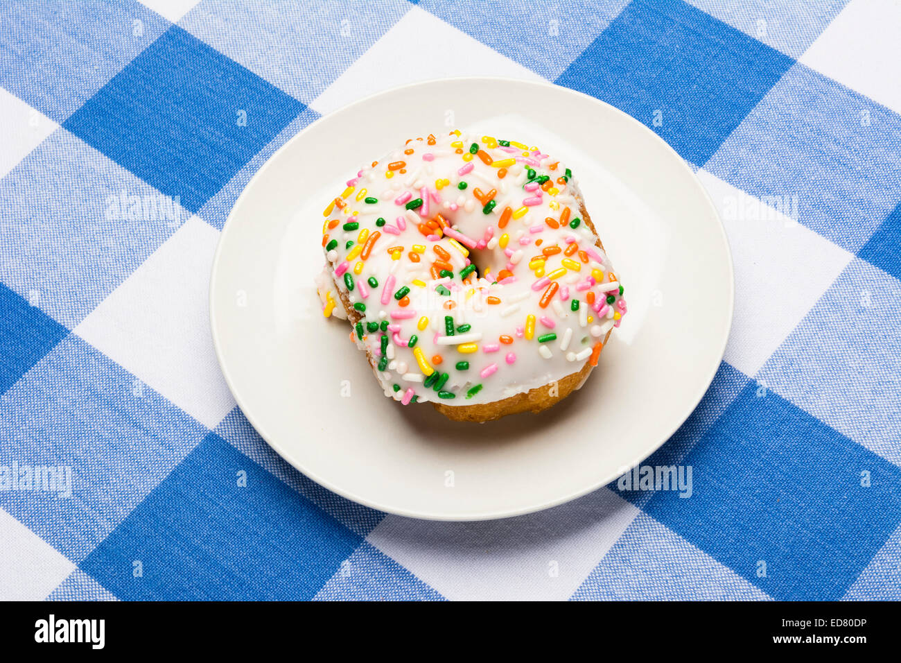 A fresh, delicious icing coated cake donut with sweet sprinkles on a classic, checkered diner tablecloth D - Stock Image
