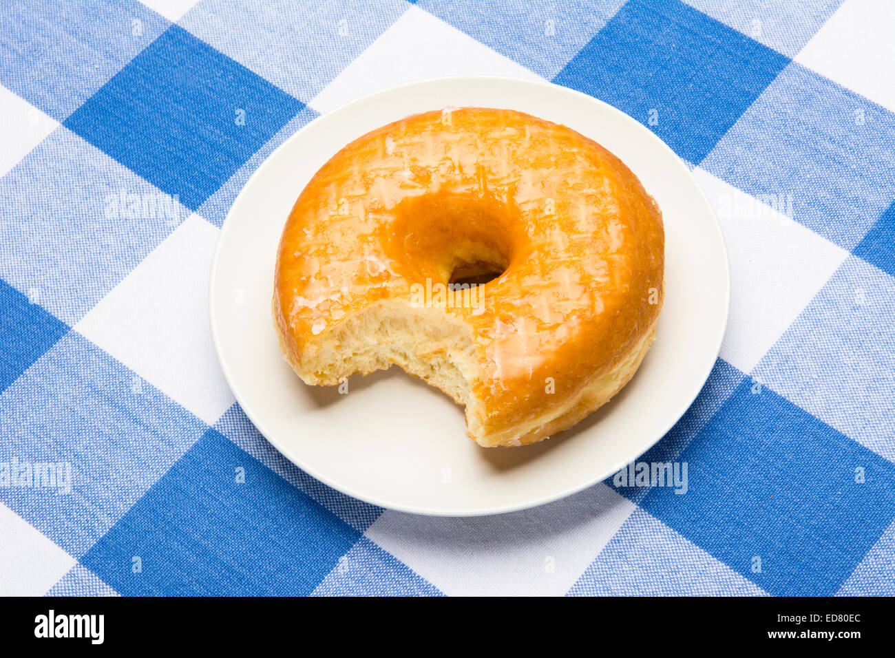 Delicious glazed donut with bite taken out during breakfast - Stock Image