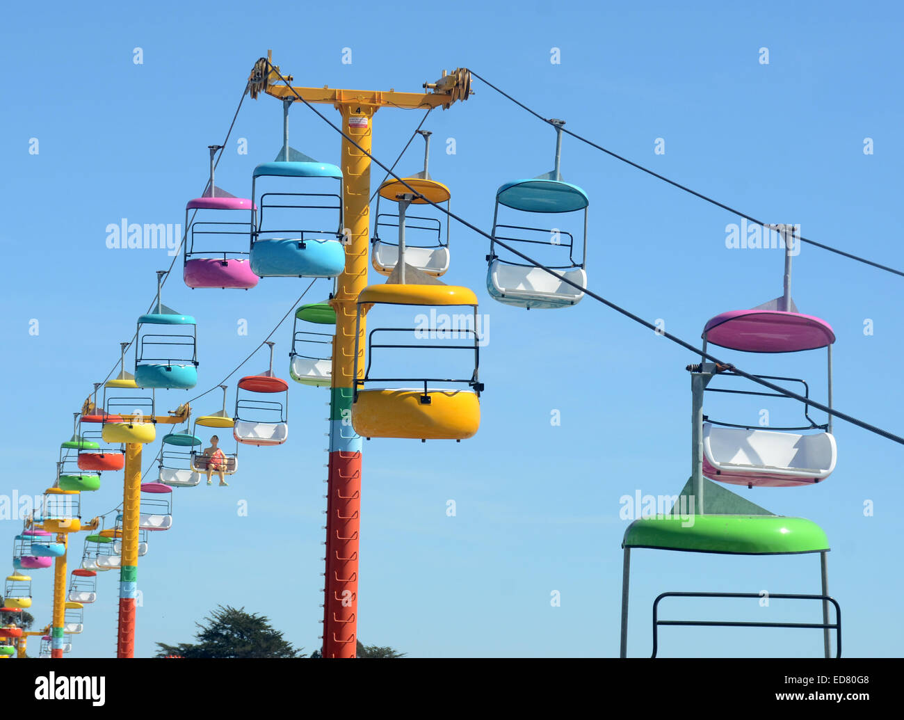 Colorful seats from amusement park ride against blue sky - Stock Image