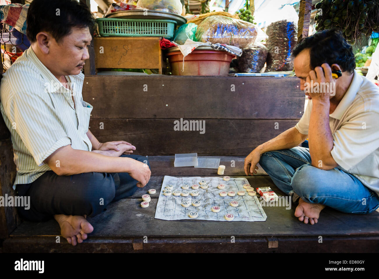 Men playing a game of Chinese chess in an alleyway at a market in Saigon - Stock Image