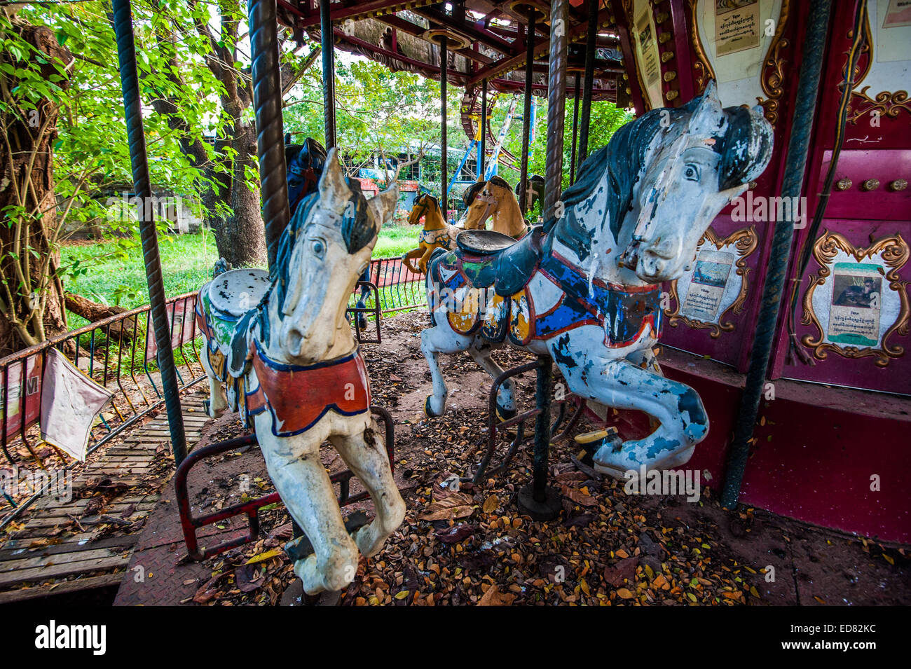 Decaying horses on carousel, at abandoned amusement park in Yangon Stock Photo