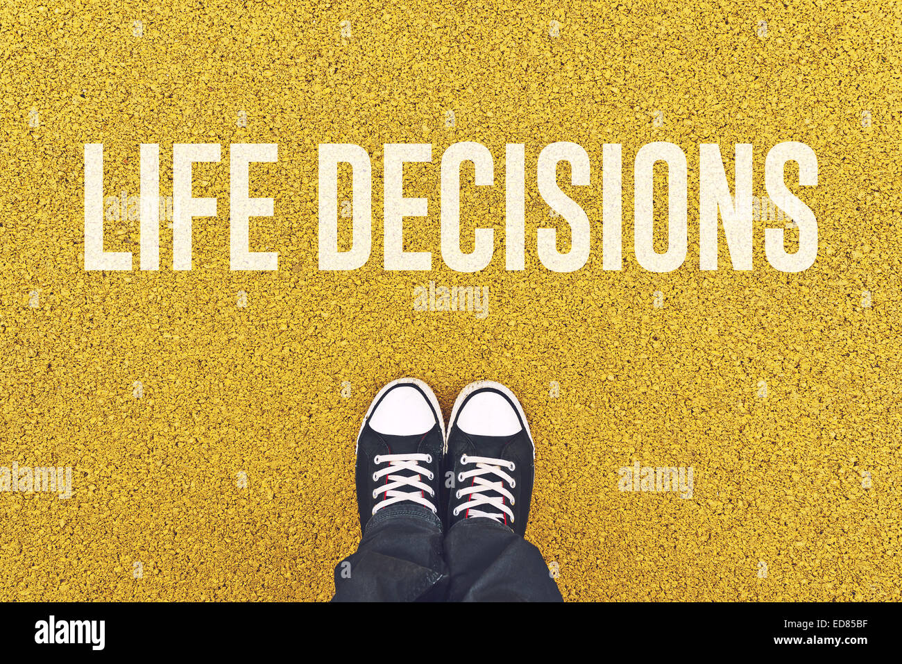 Young man standing on pavement in front of Life Decisions sign printed. - Stock Image