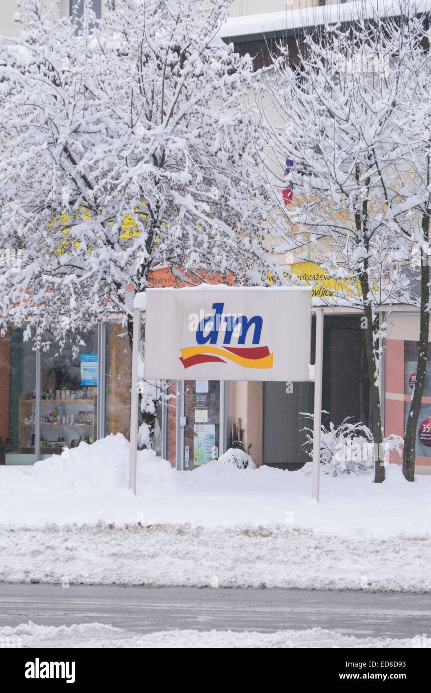 DM supermarket sign covered with snow in in Radovljica, Slovenia - Stock Image