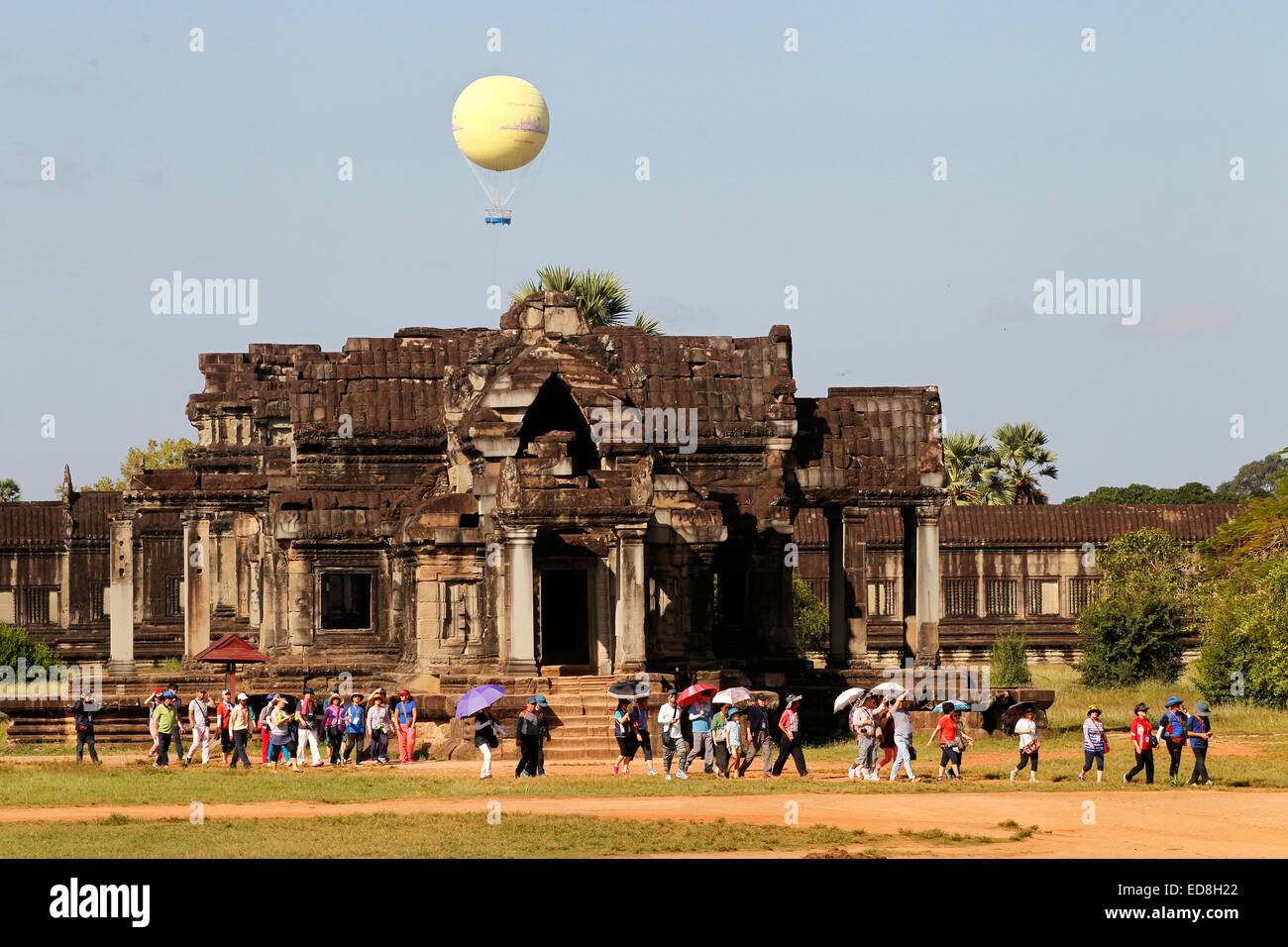 A group of tourists at Angkor Wat temple in Cambodia with the hot air balloon which ascends to allow tourists to Stock Photo