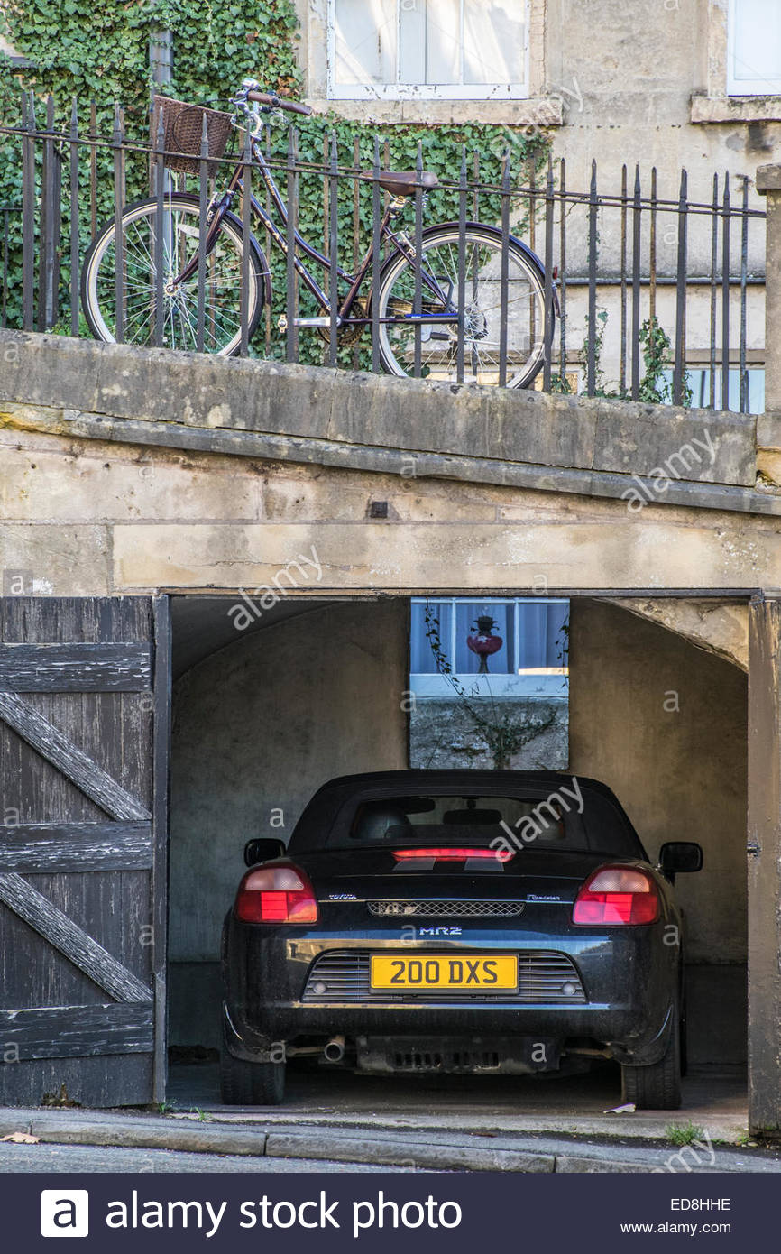 A bike parked against the railings on a raised footpath with a car parked in a garage below - Stock Image