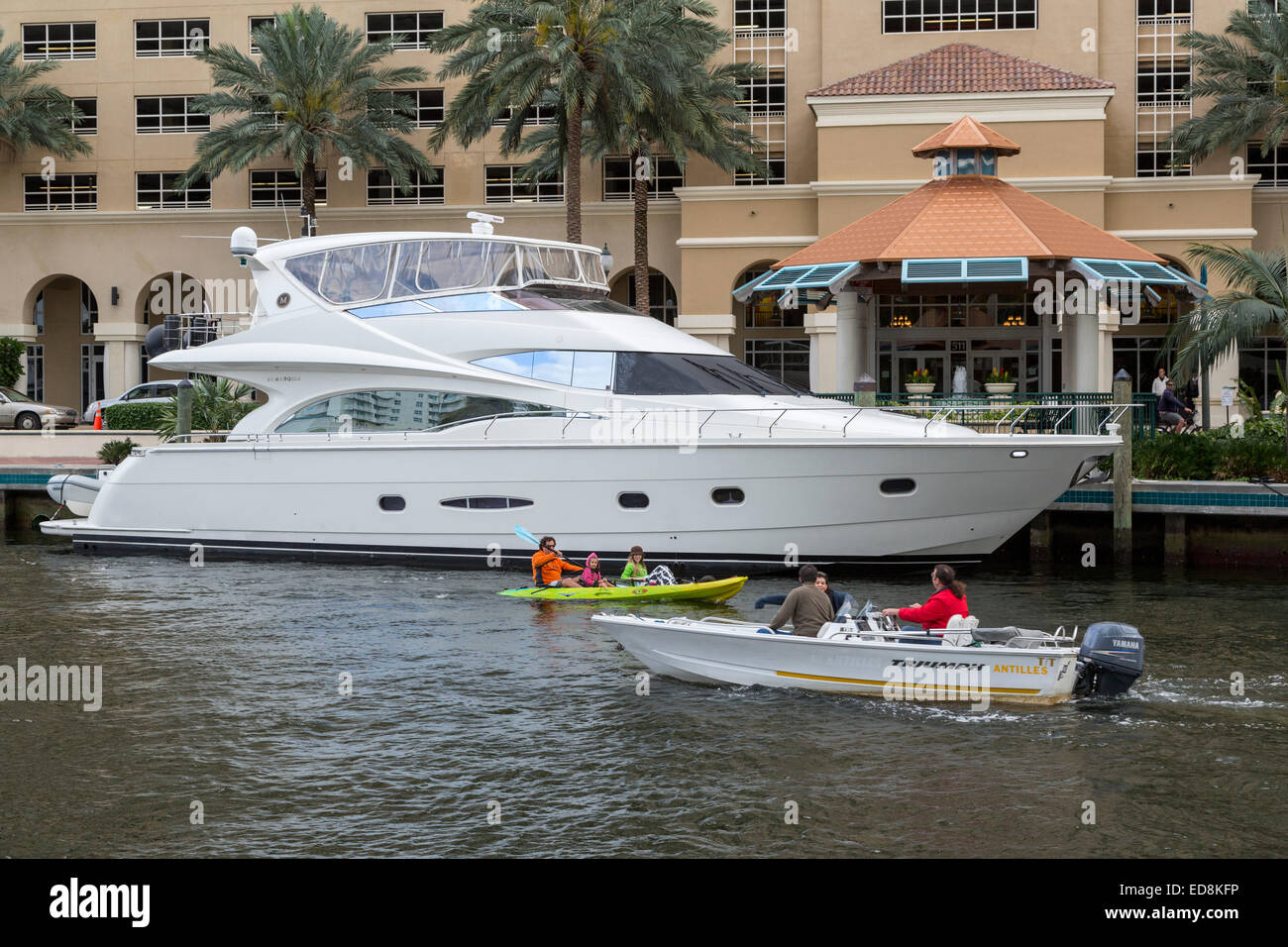 Ft. Lauderdale, Florida.  Boats on New River in front of Nu River Landing Condominium.  Juxtaposition of Life Styles - Stock Image
