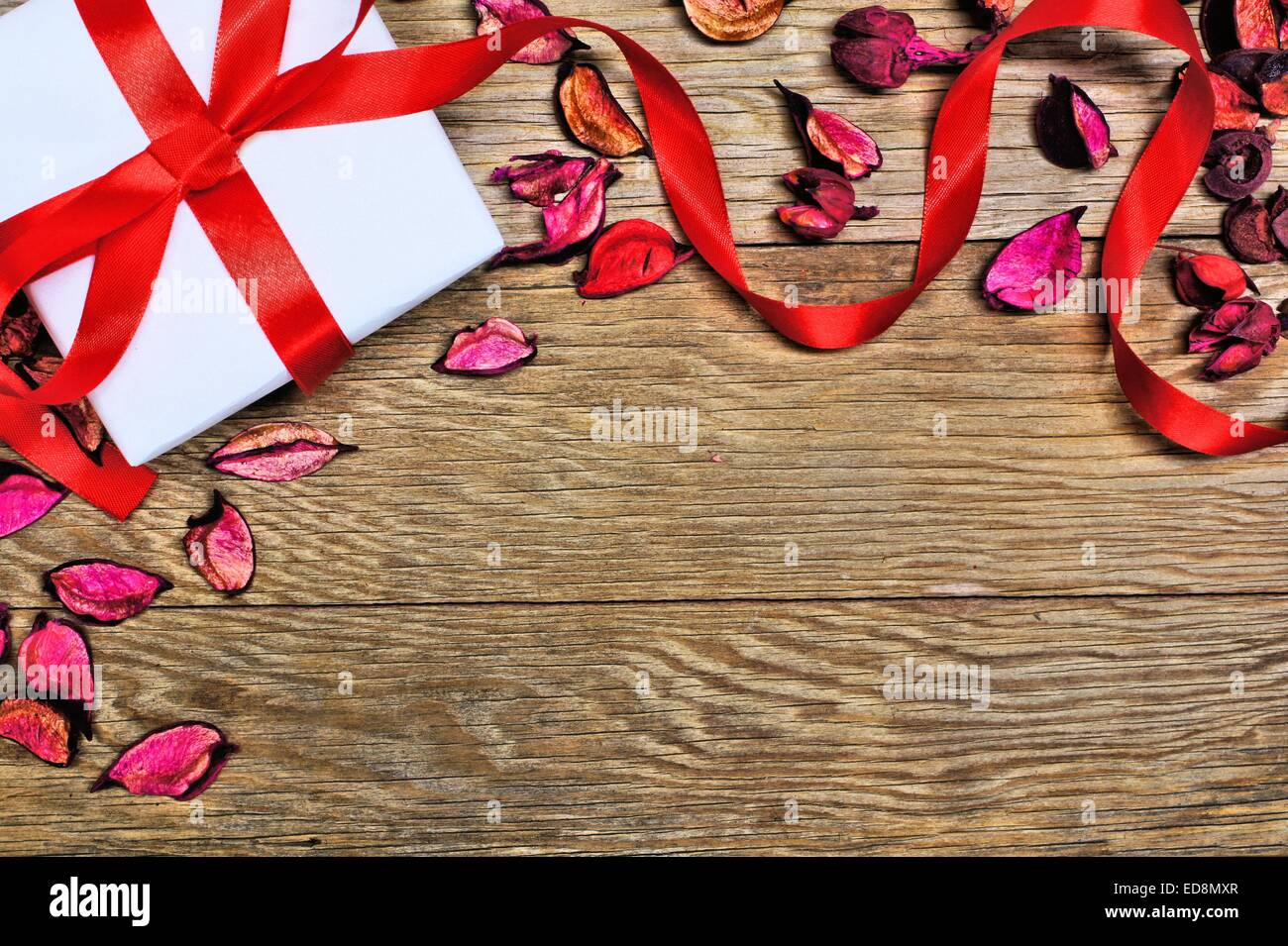 Gift box with scattered petals and ribbon on wood background Stock Photo