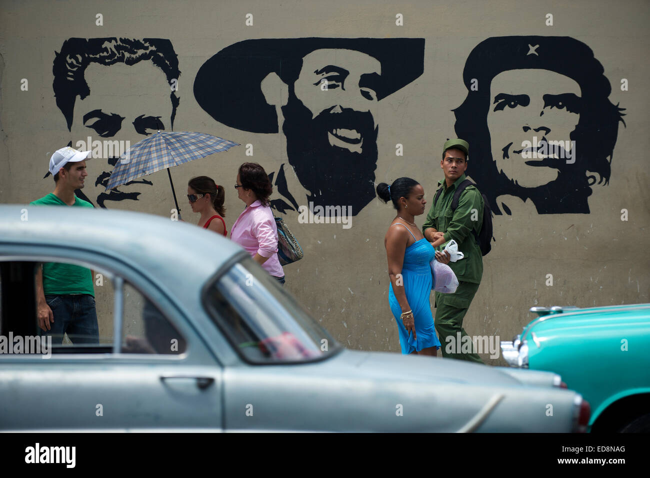 HAVANA, CUBA - JUNE, 2011: Pedestrians and classic American cars pass in front of stencil billboard of Communist - Stock Image