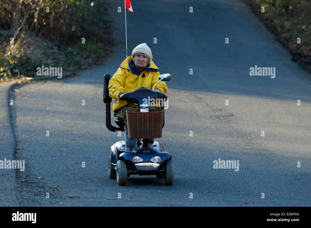 Elderly woman riding motorized medical scooter on road-Victoria, British Columbia, Canada. - Stock Image