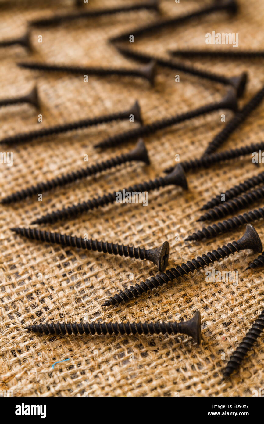 Group of used and old screws on sack fabric - Stock Image