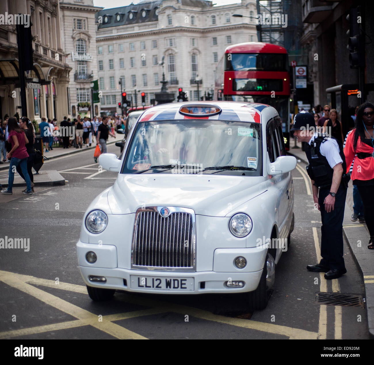 Policeman talking to London Taxi driver on Shaftesbury Avenue near Picadilly Circus, London - Stock Image