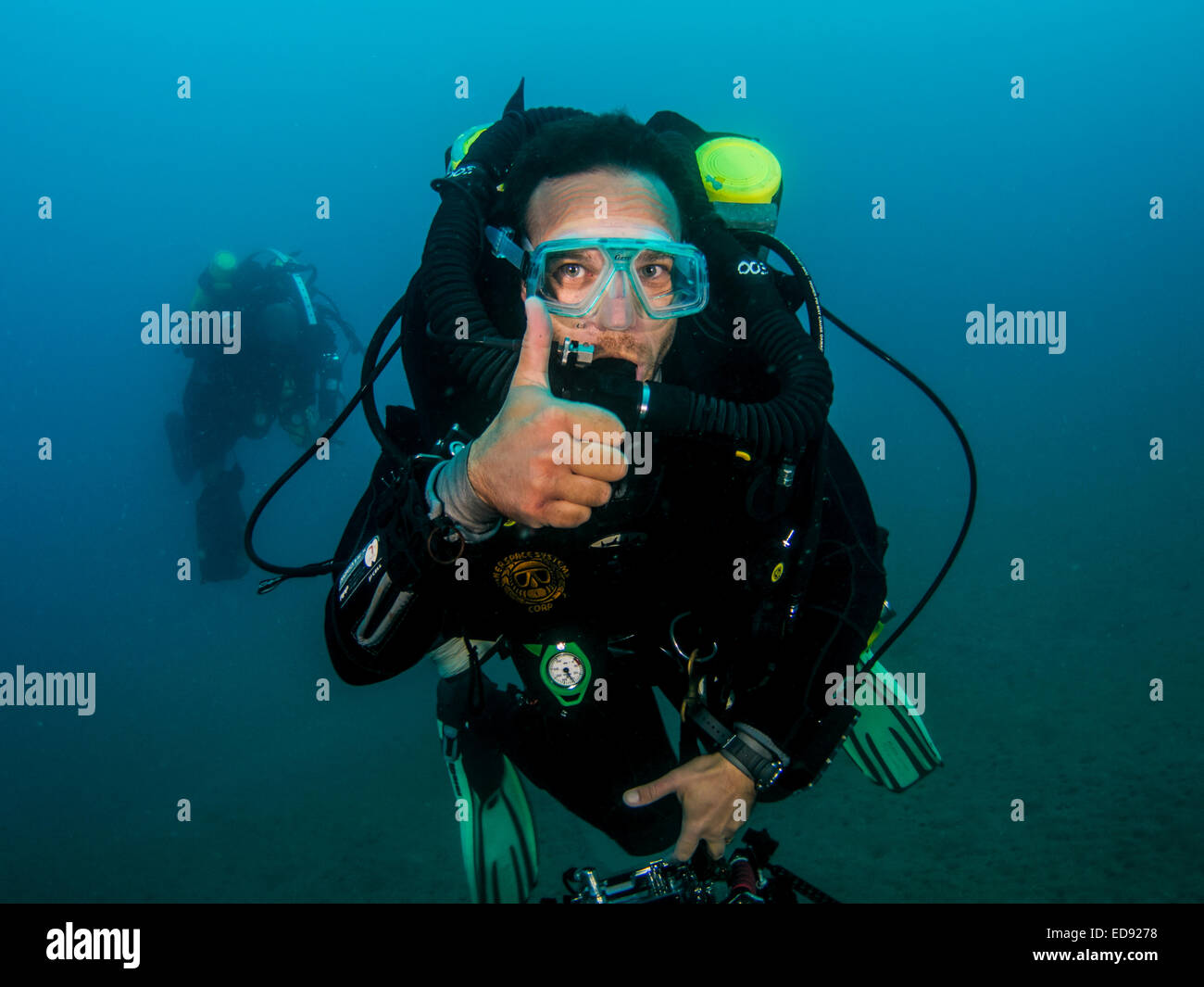 Underwater Hand signs scuba diver demonstrates the sign language for divers. Ascend, or I am going up: A fist is - Stock Image