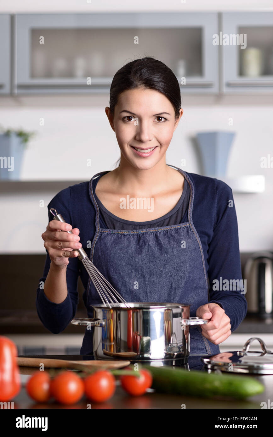 Happy friendly young housewife cooking dinner standing at the hob holding a whisk over a saucepan as she prepares - Stock Image
