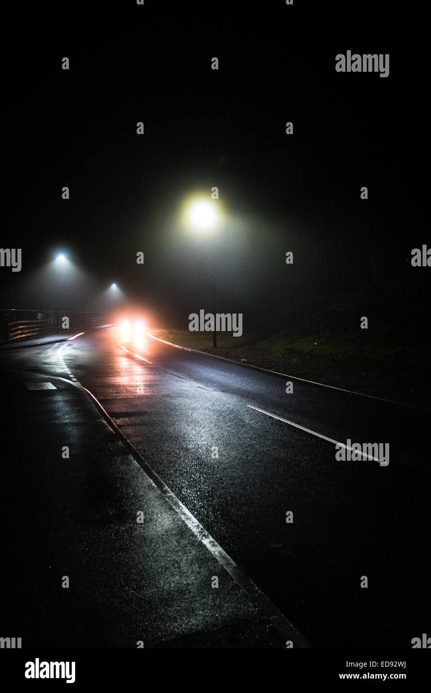 Menace and threat: Car headlights, Night-time, darkness,  streetlights, misty foggy weather, deserted road city - Stock Image