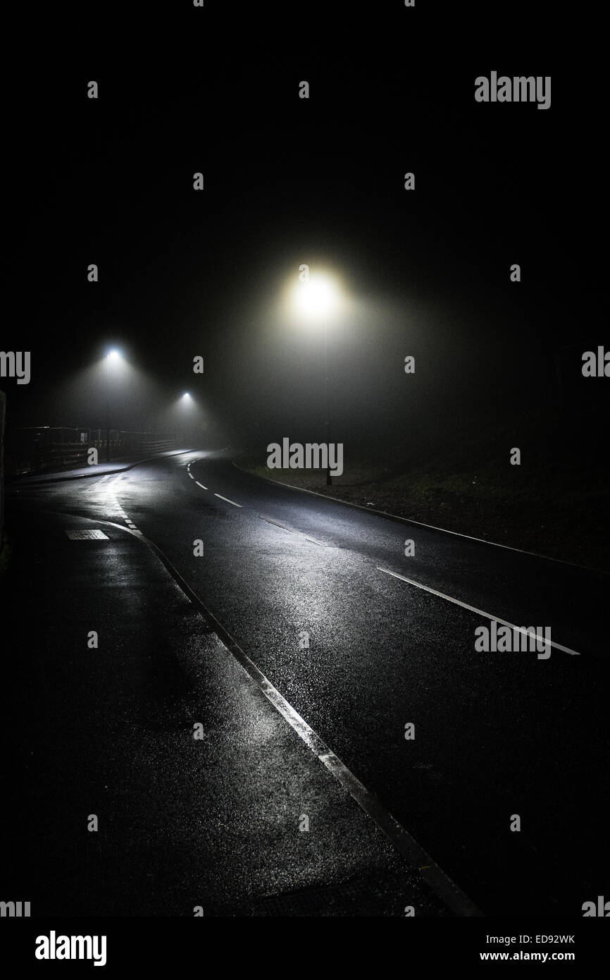 Menace and threat: Night-time, darkness,  streetlights, misty foggy weather, deserted road city street, empty road, - Stock Image