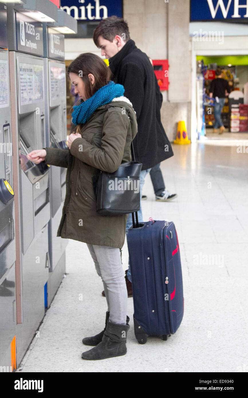 London, UK. 2nd January 2015. Passenger buying  tickets from self service ticket machines at Waterloo station. Rail - Stock Image