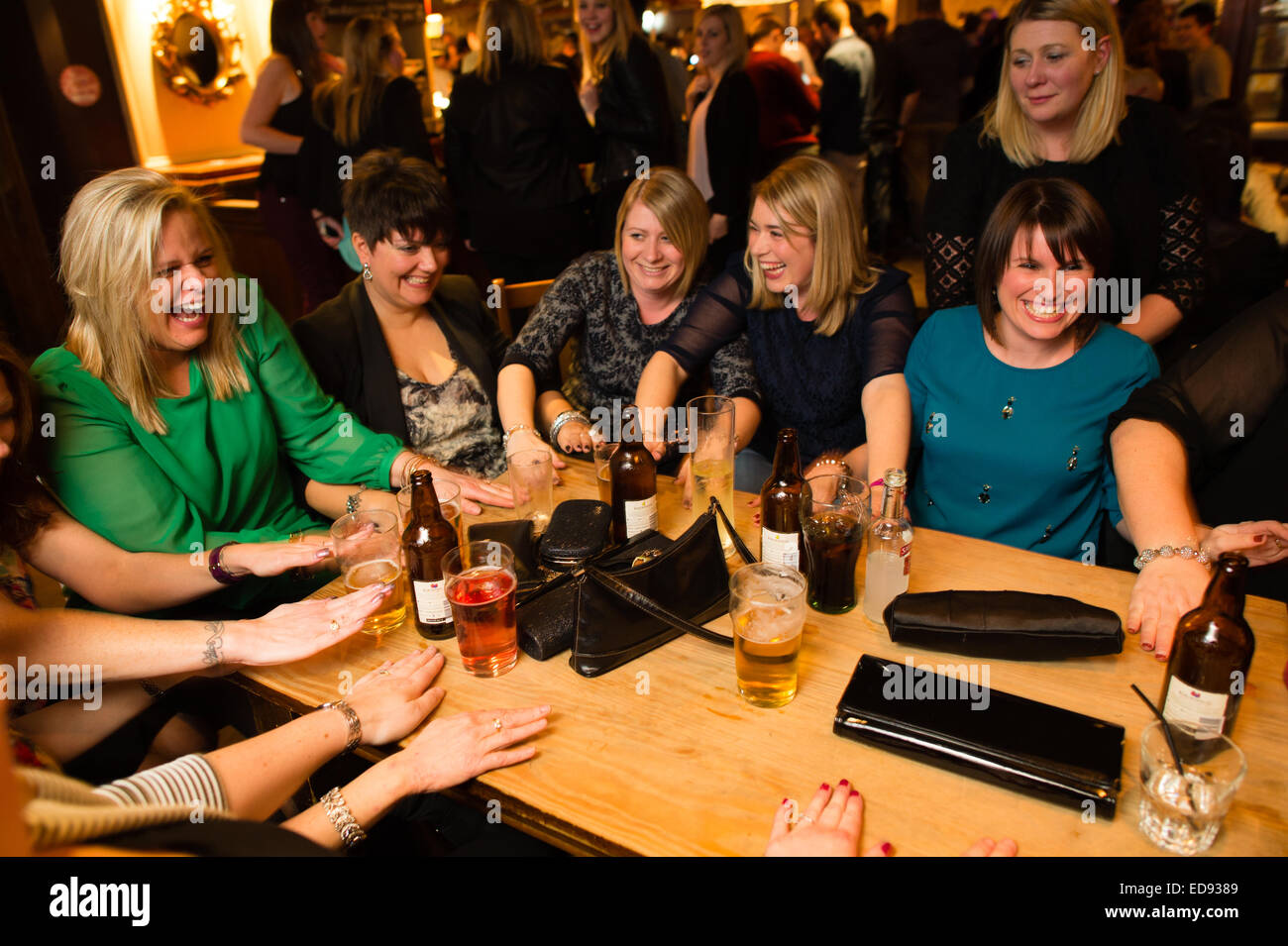 A group of women friends  laughing and enjoying themselves playing a drinking game  in a pub in Aberystwyth  Wales - Stock Image