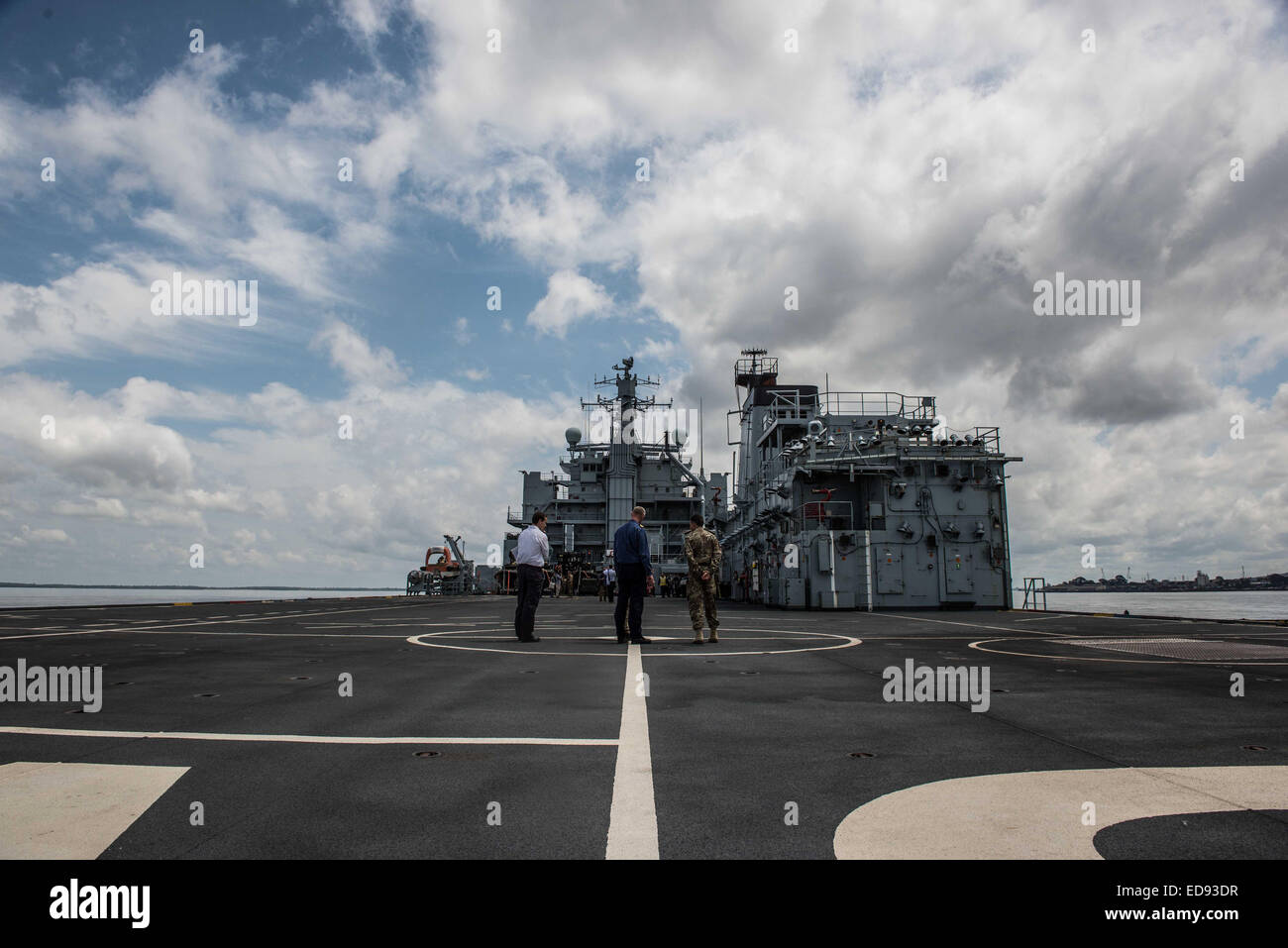 Officers talk onboard the flight deck of the RFA Argus support ship. The ship arrived in late October and is serving - Stock Image